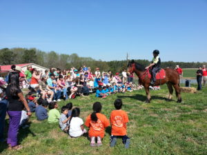 children listening to speaker on horseback