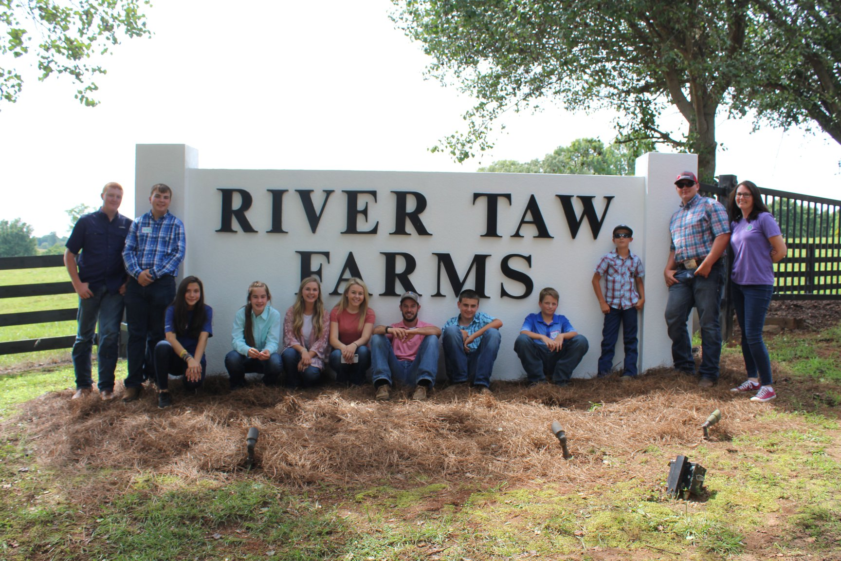 Youth in front of River Taw Farms sign